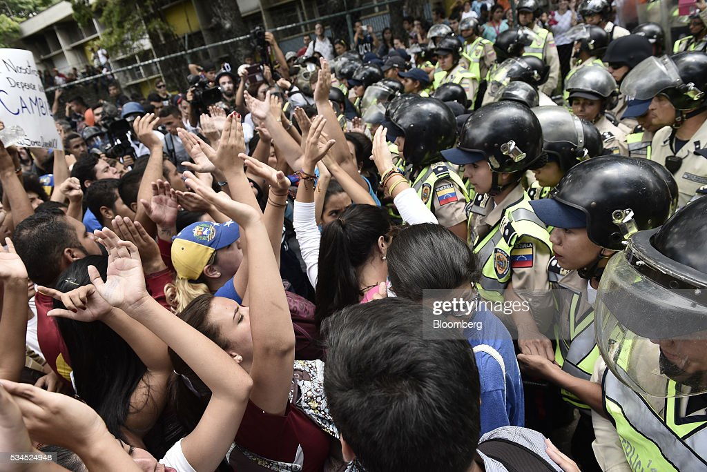 Pro-opposition students march next to Bolivarian National Police near the Central University of Venezuela in Caracas, Venezuela, on Thursday, May 26, 2016. The opposition is pushing for a recall referendum on President Nicolas Maduro and blame the 53-year-old leader for widespread shortages of food and basic necessities. Photographer: Carlos Becerra/Bloomberg via Getty Images