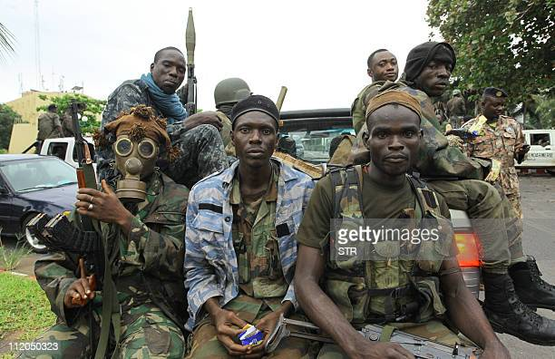 ProOuattara fighters of the FRCI one of them wearing a gas mask prepare for the socalled 'final assault' in front of the Golf Hotel in Abidjan on...