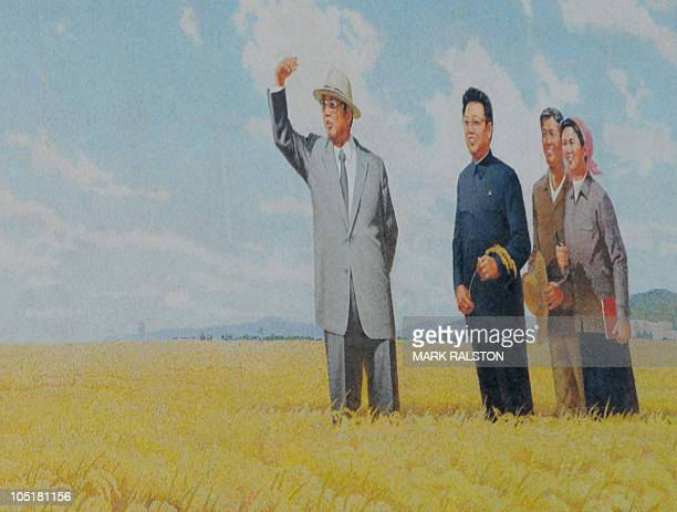 A propaganda poster showing the former North Korean leader Kim IlSung and his son current leader Kim JongIl with farmers at a farming commune outside...