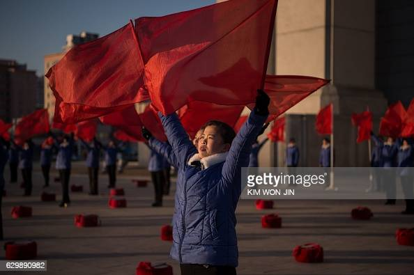 TOPSHOT A propaganda troupe perform before the Arch of Triumph on the last day of the 200day campaign in Pyongyang on December 15 2016 North Korea...