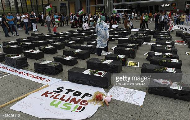 A proPalestine demonstrator walks through mockups of children's coffins during a rally in the streets of Berlin to express solidarity with the...