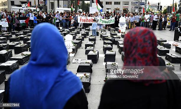 ProPalestine demonstrators stand next to mockups of children's coffins during a rally in the streets of Berlin to express solidarity with the...
