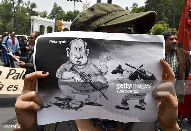 A proPalestinian activist holds a cartoon depicting Israeli Prime Minister Benjamin Netanyahu during a rally against the Israeli military offensive...