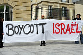 ProPalestinian activists hold a banner reading 'Boycott Israel' outside the Organisation for Economic Cooperation and Development headquarters on May...