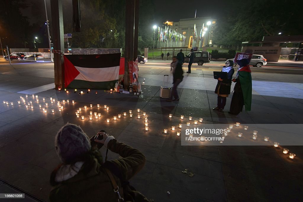 Pro-Palestinian demonstrators stand next to candles during a protest against the Israeli offensive in Gaza on November 21, 2012 in front of the United Nations Office in Geneva. A ceasefire agreed between Israel and Hamas officially came into effect on the basis of the text of the deal announced shortly beforehand in Egypt.