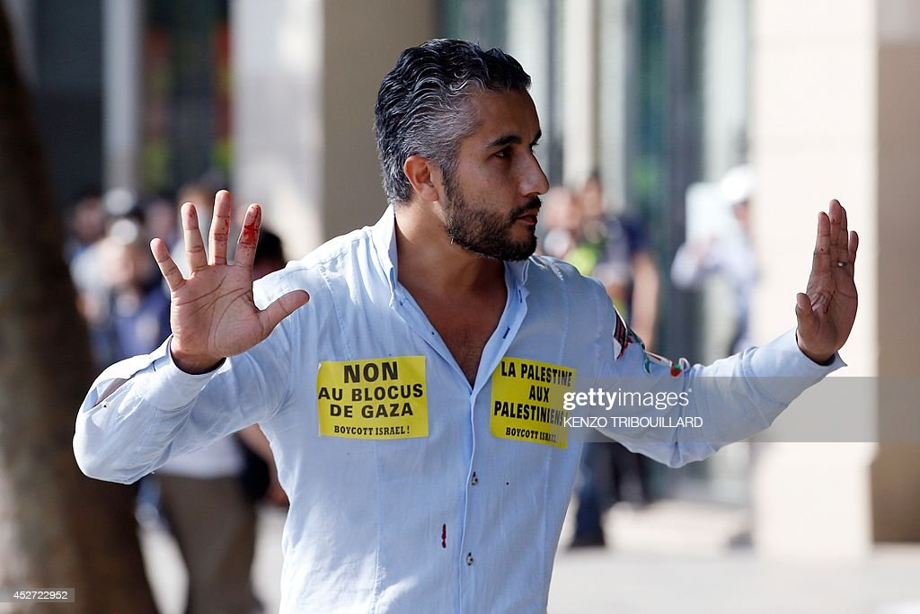 A pro-Palestinian supporter raises his hand on the Republique square in Paris, during a banned demonstration against Israel's military operation in Gaza and in support of the Palestinian people, on July 26, 2014. French authorities banned on July 26, 2014 a new pro-Palestinian demonstration over concerns it could turn violent as previous rallies have, but demonstrators may ignore the ban as they did last weekend. US Secretary of State John Kerry and other top diplomats from Europe and the Middle East began talks in Paris on July 26 to press efforts for a long-term ceasefire between Israel and Hamas.