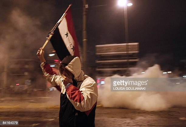 A proPalestinian supporter runs from tear gas during clashes outside the Israeli embassy in Athens on January 3 Thousands of proPalestinian...
