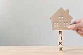 "Property investment and house mortgage financial. Risk management concept. Hand putting wooden home on wood block with word ""risk"""