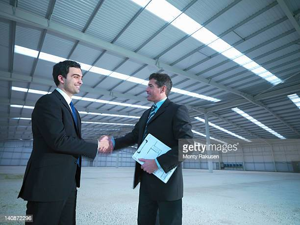Property managers shaking hands in finished factory building
