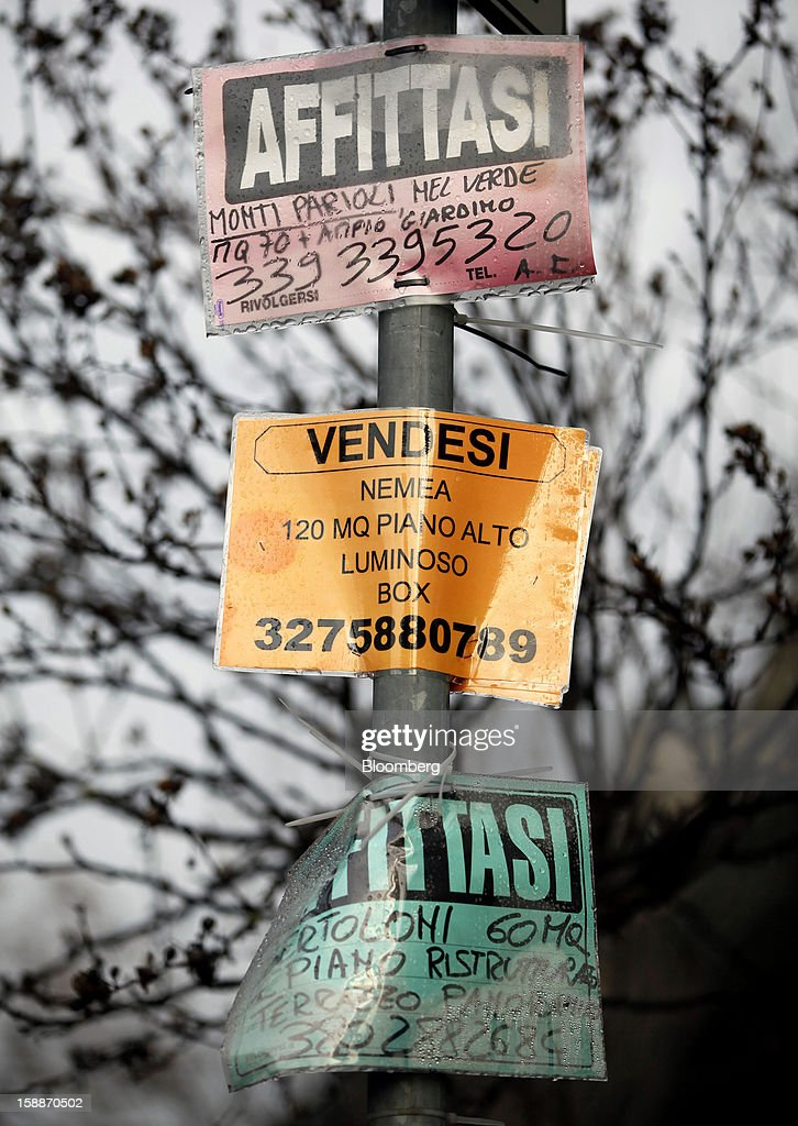 Property sale, center, and rental signs hang from a street lamp near residential apartment blocks in the Parioli district of Rome, Italy, on Wednesday, Jan. 2, 2013. Italian property sales often are reported to be less than the actual price paid to reduce taxes or skirt controls on money laundering, according to the website of the finance police, which reports to Italian Finance Minister Vittorio Grilli. Photographer: Alessia Pierdomenico/Bloomberg via Getty Images