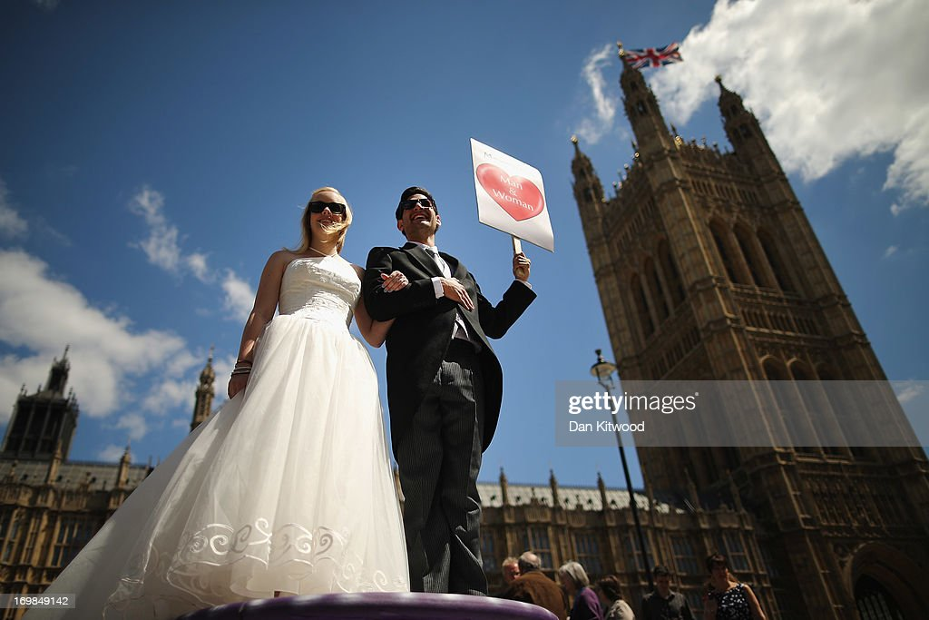 Proponents of single sex marriage dressed as a bride and groom, Carrie Hardy, and Martin Etchart of Argentina, stand outside the Houses of Parliament on June 3, 2013 in London, England. A government bill allowing same sex marriage in England and Wales was passed in the House of Commons last month, despite the opposition of 133 Conservative MP's. The bill will be debated later today in the House of Lords.