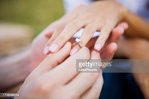 Feminino e masculino mão vestindo engagment Anel