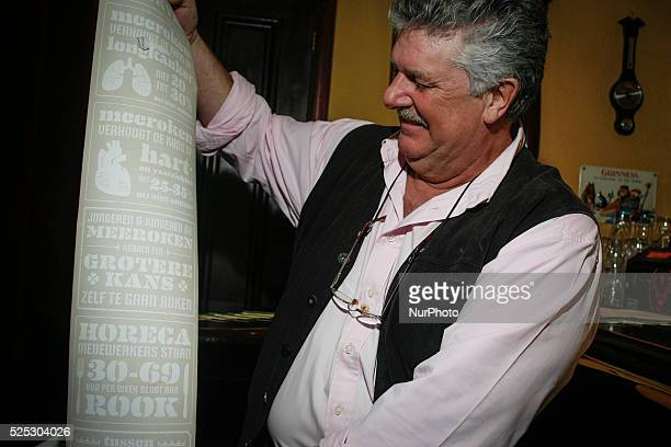 Proprietor of the oldest pub in The Hague Bart van Dam shows a paper rol with statistics printed on it informing on the harmful effects of smoking...