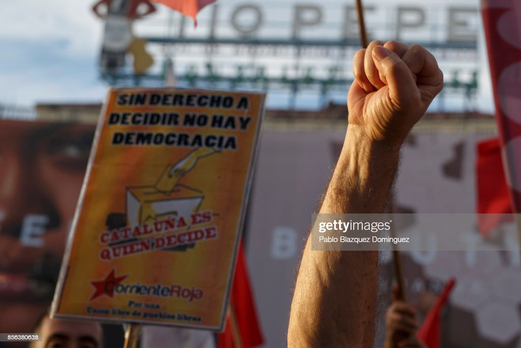 Pro-referendum demonstrator rises his fist next to a placard reading 'If there is not right to decide, there is no democracy. Catalonia decides' during a protest in support of Catalan's referendum and against government repression as Catalonian voted in a referendum on October 1, 2017 in Madrid, Spain. More than five million elegible Catalan voters are estimated to visit 2,315 polling stations today for the Catalonia's referendum on independence from Spain. The Spanish government in Madrid has declared the vote illegal and undemocratic.