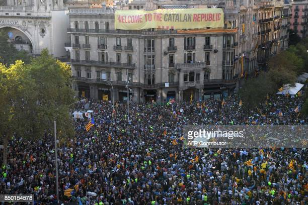 Proreferendum demonstrators gather in front of a building with a banner reading 'Welcome to the Catalan republic' during a protest near the Economy...
