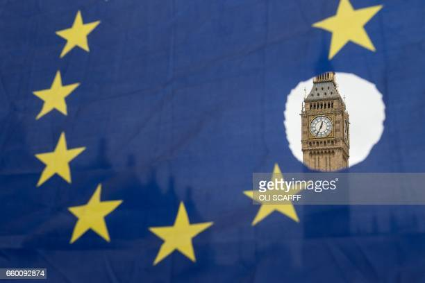 A proremain protester holds up an EU flag with one of the stars symbolically cut out in front of the Houses of Parliament shortly after British Prime...