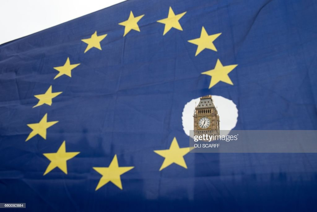 A pro-remain protester holds up an EU flag with one of the stars symbolically cut out in front of the Houses of Parliament shortly after British Prime Minister Theresa May announced to the House of Commons that Article 50 had been triggered in London on March 29, 2017. Prime Minister Theresa May today said there could be 'no turning back' and called for national unity, after notifying the EU of Britain's intention to end its 44-year membership of the bloc. /