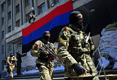 A proRussia activist hangs a flag of the socalled 'People's Republic of Donetsk' on the regional administration building seized by separatists as...