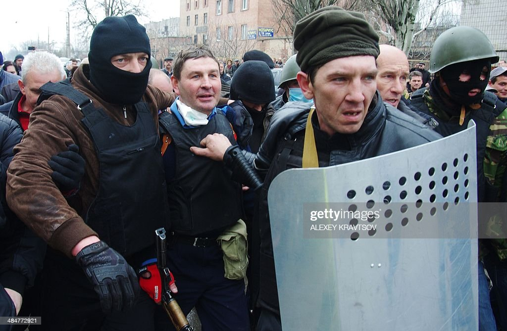 Pro-Russia militiamen detain the head of the regional police after storming the regional police building in the eastern Ukrainian city of Horlivka (Gorlovka), near Donetsk, on April 14, 2014. A few hundred pro-Russia activists seized the building after an hour-long storming. Ukraine's interim president on April 14 made a dramatic about-face aimed at defusing tensions in the separatist east by backing a national referendum on turning the ex-Soviet republic into a federation with broader regional rights.
