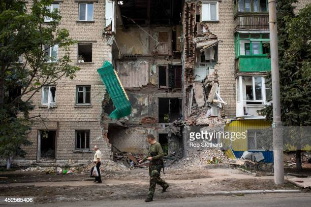 A proRussia rebel and a local resident walk past an apartment building damaged by rocket fire on July 23 2014 in Snizhne Ukraine Rockets struck the...