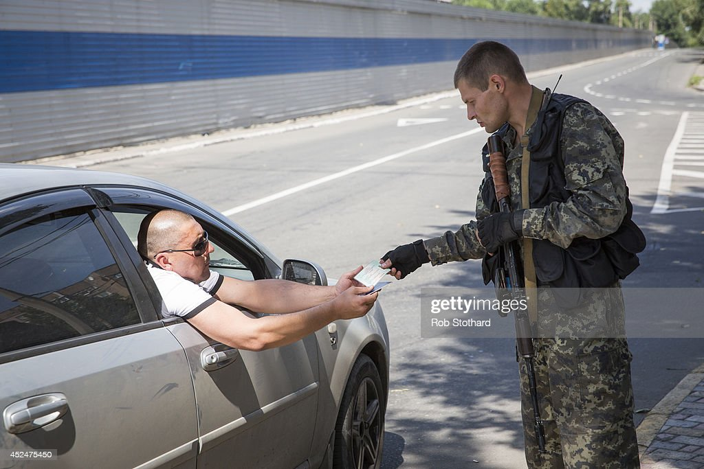 A pro-Russia rebel checks a man's identification at a checkpoint near the central railway station on July 21, 2014 in Donetsk, Ukraine. Local authorities warned residents in the area not to go outside or leave their homes whilst intense shelling set a market ablaze close to the station. The security situation is continuing to affect the investigation into the Malaysian Airlines flight MH17 crash and it is still unclear where or when the train containing the bodies of victims will be moved. Malaysian Airlines flight MH17 was travelling from Amsterdam to Kuala Lumpur when it crashed killing all 298 on board including 80 children. The aircraft was allegedly shot down by a missile and investigations continue over the perpetrators of the attack.