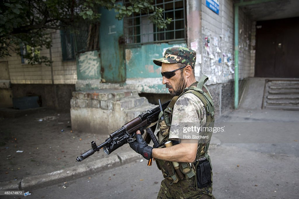 A pro-Russia rebel patrols a residential area close to the central railway station on July 21, 2014 in Donetsk, Ukraine. Local authorities warned residents in the area not to go outside or leave their homes whilst intense shelling set a market ablaze close to the station. The security situation is continuing to affect the investigation into the Malaysian Airlines flight MH17 crash and it is still unclear where or when the train containing the bodies of victims will be moved. Malaysian Airlines flight MH17 was travelling from Amsterdam to Kuala Lumpur when it crashed killing all 298 on board including 80 children. The aircraft was allegedly shot down by a missile and investigations continue over the perpetrators of the attack.