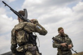 ProRussia rebels guard the area around the wreckage of Malaysia Airlines flight MH17 during monitoring by investigators from Malaysia and the...