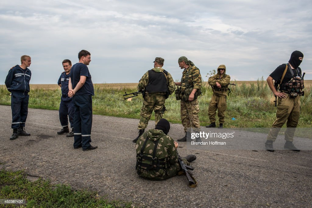 Pro-Russia separatist fighters and emergency personnel gather near the scene of the crash of Malaysia Airlines flight MH 17 on July 19, 2014 in Grabovo, Ukraine. Malaysia Airlines flight MH17 was travelling from Amsterdam to Kuala Lumpur when it crashed killing all 298 on board including 80 children. The aircraft was allegedly shot down by a missile and investigations continue over the perpetrators of the attack.