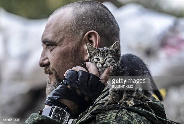 A proRussia separatist pets a kitten standing on his shoulder as he mans a checkpoint in the northern outskirts of city of Donetsk on July 22 2014...