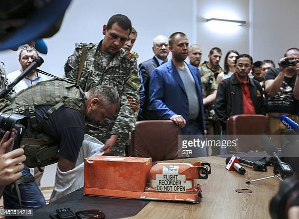 A proRussia separatist shows members of the media a black box belonging to Malaysia Airlines flight MH17 before handing it over to Malaysian...