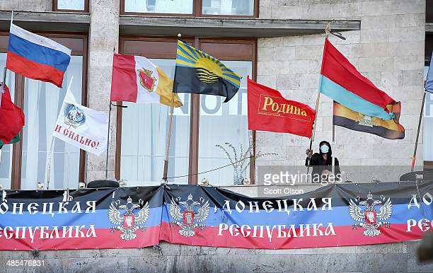 A proRussian activist raises a flag on a balcony of Donetsk Regional Administration building on April 18 2014 in Donetsk Ukraine The activists who...