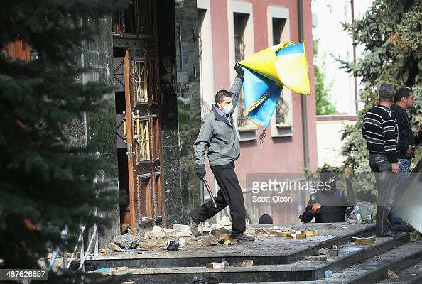 A proRussian activist removes a Ukrainian flag from the prosecutors office after it was overrun on May 1 2014 in Donetsk Ukraine Activists marched to...
