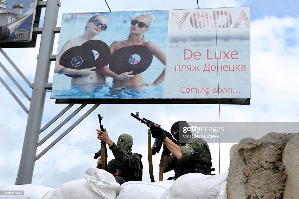 Pro-Russian armed militants stand guard at a barricade and check-point, below an advertising sign, in the eastern Ukrainian city of Donetsk on June 1, 2014. Ukraine's new pro-Western leader enters a defining week today seeking to head off a Russian gas cut and secure US President Barack Obama's backing with his country threatened by civil war.