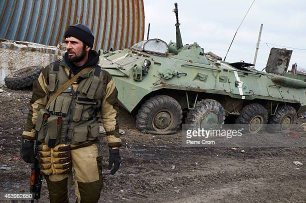 A proRussian fighter from Chechnya stands near a damaged Ukrainian armoured vehicle on February 20 2015 in Debaltseve Ukraine The strategic railway...