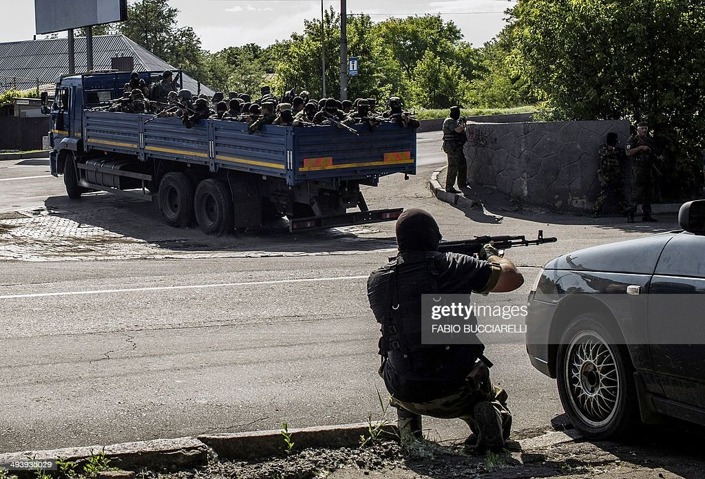 A proRussian fighter takes position behind a car as a truck full of proRussian fighters heads towards the battle during clashes against Ukrainian...