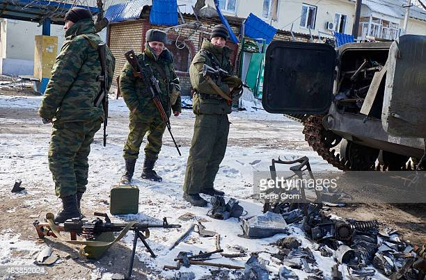 ProRussian fighters stand guard near a destroyed Ukrainian armored vehicle as people from the ministry for civil defense and emergencies of the...