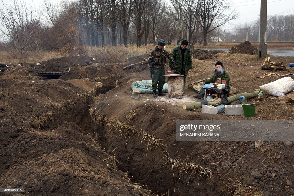 ProRussian gunmen guard next to their trenches fighting position at the Oktyaber neighborhood north west of Donetsk near the destroyed airport on...