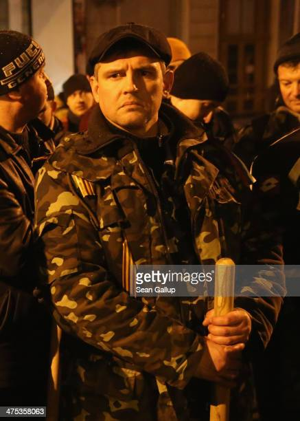 ProRussian men armed with clubs gather outside the Crimea regional parliament building after parliamentarians voted for a May 25th referendum on...