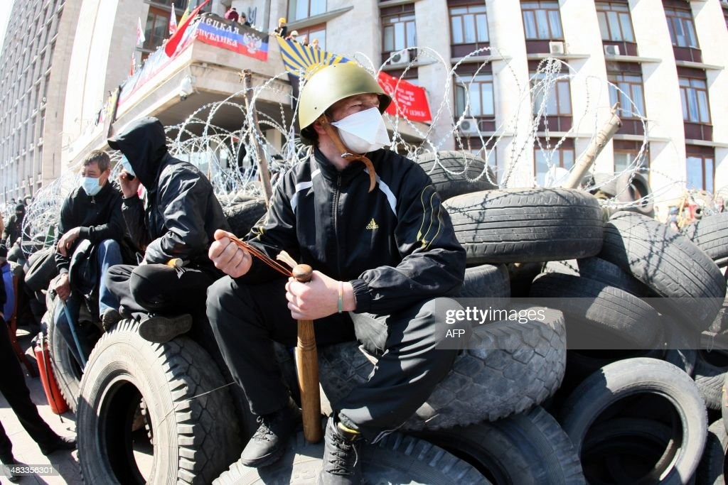 A pro-Russian militant holding a bat guards a barricade in front of the Donetsk regional administration building on April 8, 2014. Ukraine mounted a counteroffensive on April 8 by vowing to treat the separatists as 'terrorists' and making 70 arrests in a nighttime security sweep, while hundreds of militants remained holed inside the Donetsk administration building a day after proclaiming the creation of an independent 'people's republic' and demanding that an independence referendum be held before May 11. AFP PHOTO / ALEXANDER KHUDOTEPLY