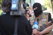 A proRussian militant is interviewed by Bulgarian journalists as he stands guard outside the Ukraine Security Service building on April 26 2014 in...