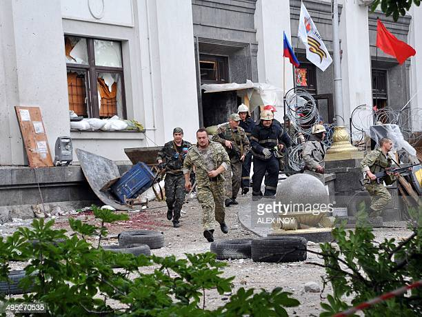 ProRussian militants and firemen run away as they leave the Regional State building they seized during a shootout with Ukrainian border guards...