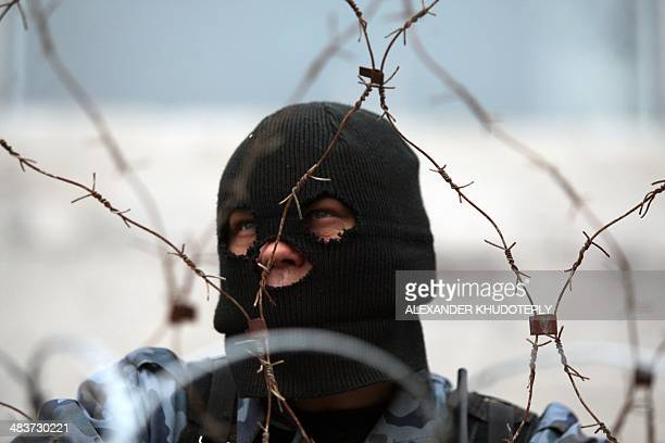 A proRussian protester guards a barricade outside the regional state administration building in the eastern Ukrainian city of Donetsk on April 10...