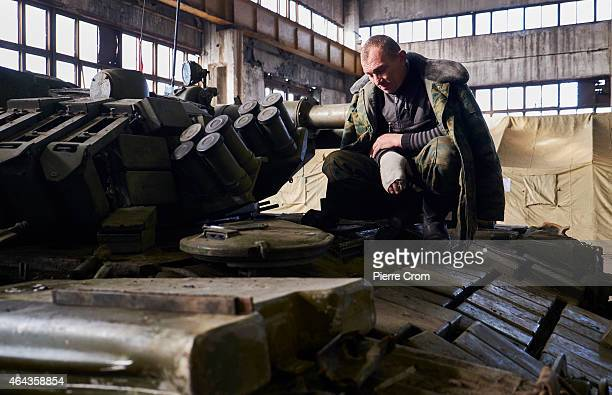 ProRussian rebel of the Separate Repair and Refurbishment Battalion touches his injured arm as he and some of his battalion make repairs on seized...