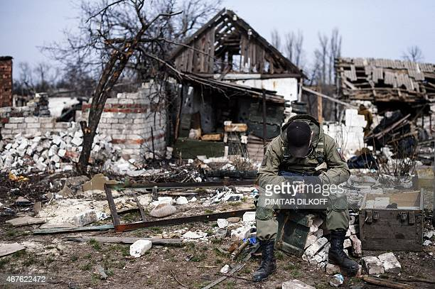 A proRussian rebel sits in front of destroyed houses in the village of Lohvynove near the eastern Ukrainian town of Debaltseve on March 26 2015 The...
