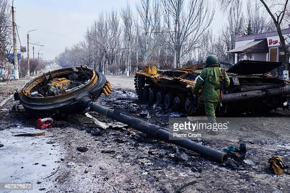 A proRussian rebel walks by a destroyed Ukrainian tank on February 7 2015 in Uglegorsk Ukraine According to ProRussian rebels control of Uglegorsk on...