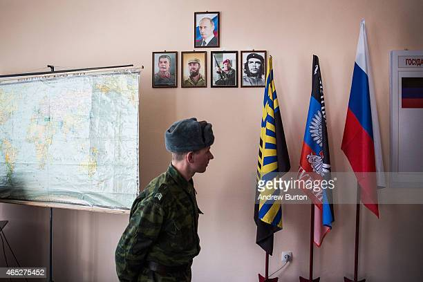 A proRussian rebel walks past a portrait of Russian President Vladmir Putin and procommuntist leaders at Battalion Kalmius headquarters on March 5...