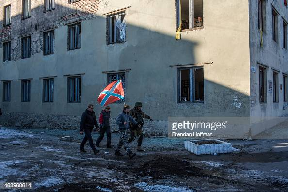 ProRussian rebels carry the flag of their selfproclaimed republic of Novorossiya past a damaged building on the central square on February 20 2015 in...