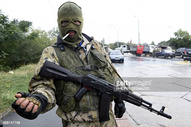 A ProRussian separatist fighter holds a grenade as he stands guard at a check point on September 10 2014 on a road of the Donetsk airport Ukrainian...