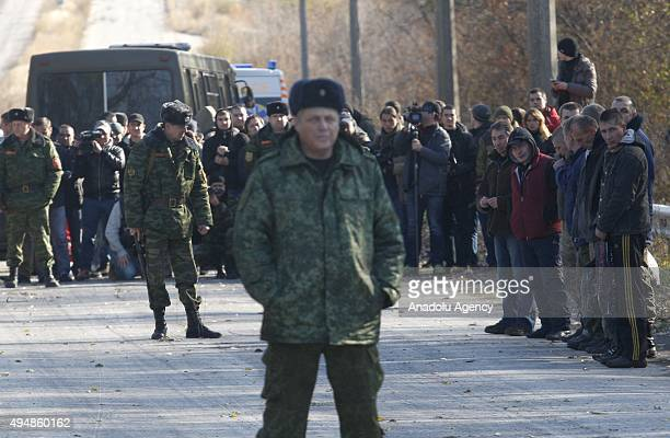 ProRussian separatists stand in line as they wait for exchange of prisoners near Schastie village in Luhansk eastern Ukraine Thursday Oct 29 2015...