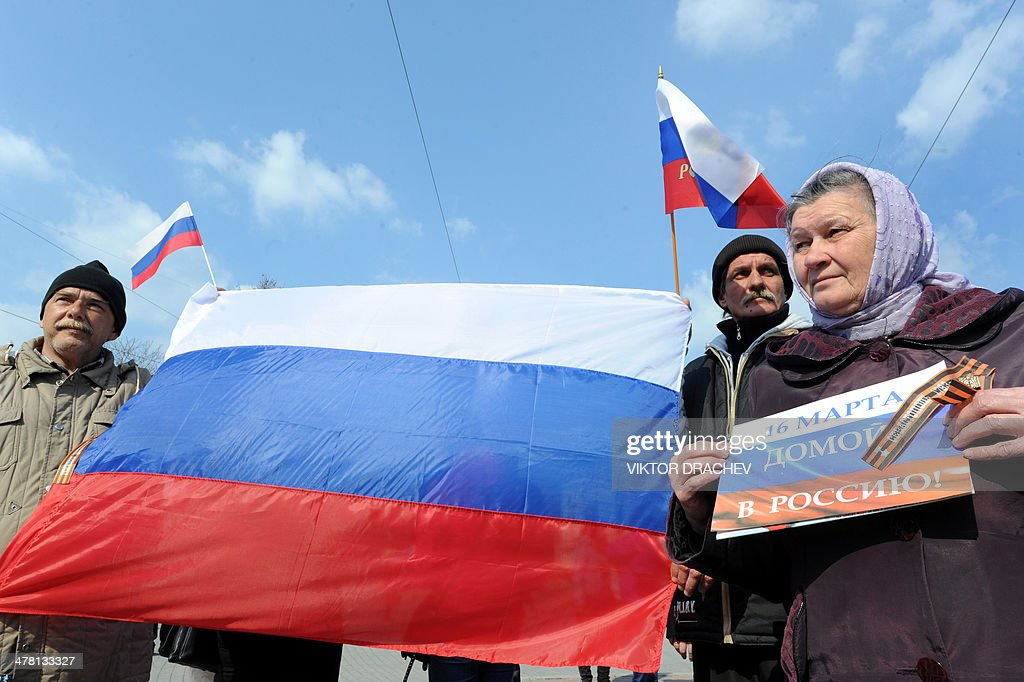 Pro-Russian supporters hold the flag and placard reading '16 March. Back home to Russia'during the rally in Sevastopol bay on March 12, 2014. Ukraine will not intervene militarily in the separatist peninsula of Crimea, in order to avoid exposing its eastern border, Ukraine's acting president told AFP Tuesday in an exclusive interview.